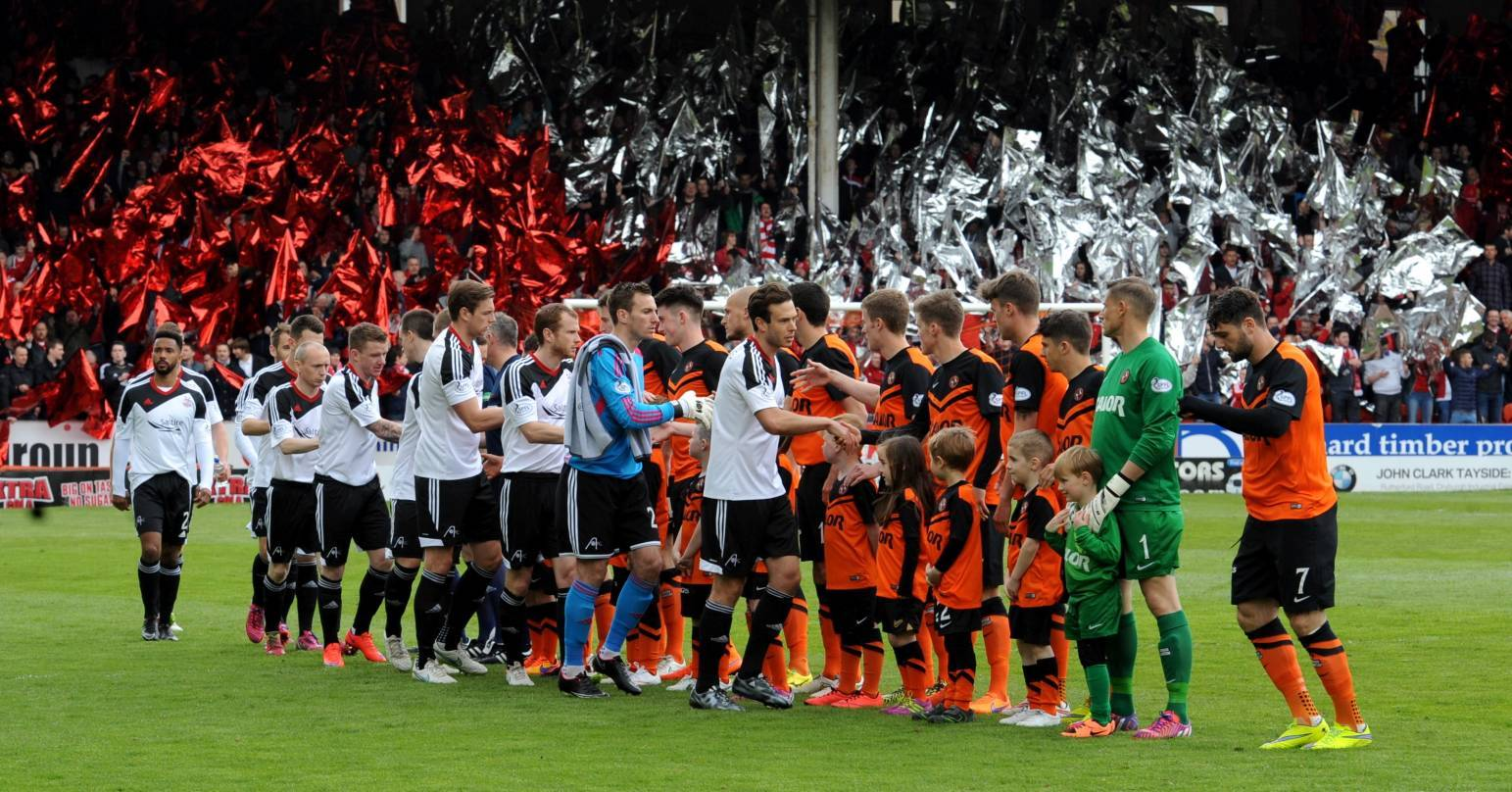 Dons and Dundee United players shake hands before the game.