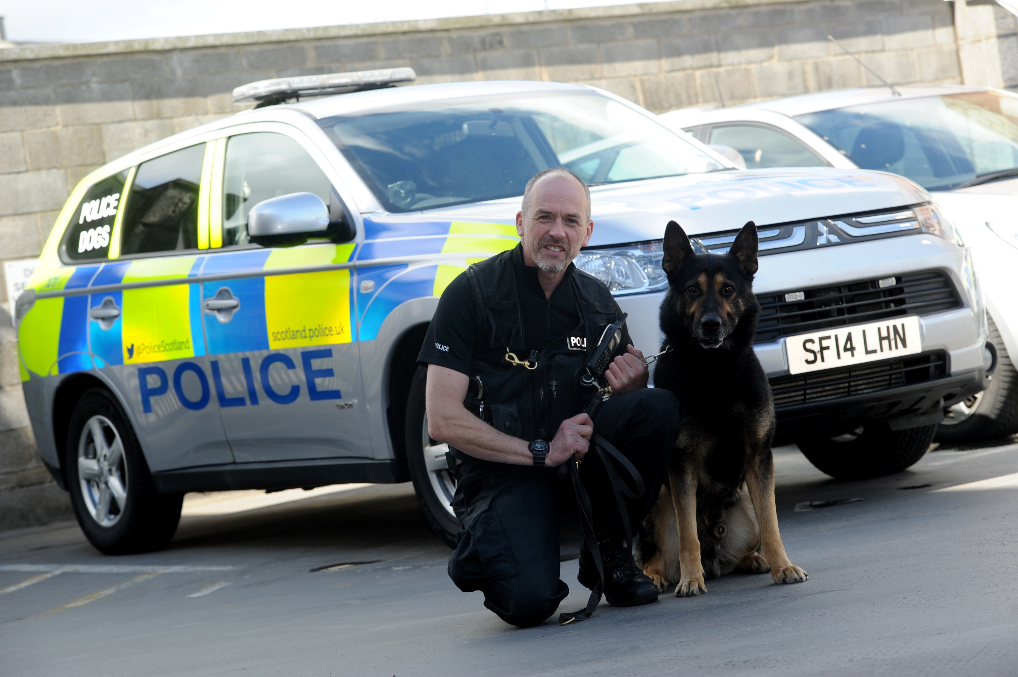 Dog handler Colin Hunter is retiring after 30 years. He is pictured with Yogi the German Shepherd.