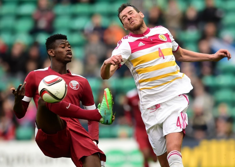 Scotland's Gordon Greer loses out to Mohammed Muntari (left)