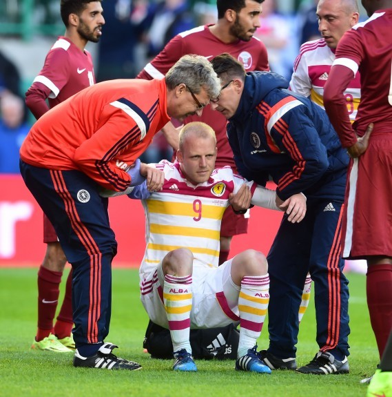Scotland staff help Steven Naismith back to his feet after a knock