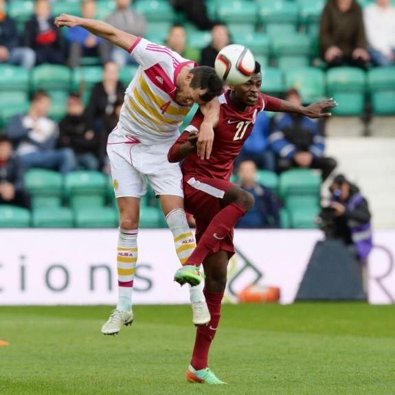 Scotland's Gordon Greer challenges in the air against Mohammed Muntari (right)
