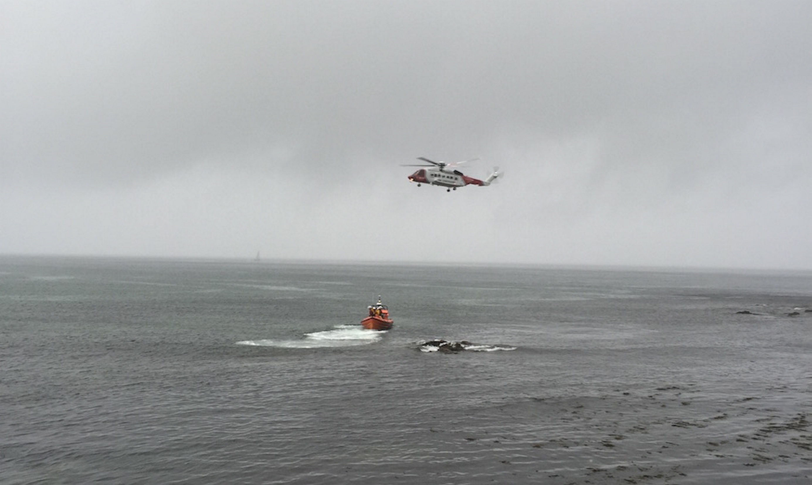 RNLI lifeboat Lydia Macdonald and Coastguard helicopter Rescue during a search following reports of a person in the water near the Union Road filling station in MacDuff.