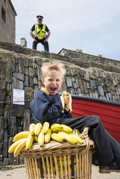The a-peel of eating a banana proves too much for Portsoy Primary pupil Mason Taylor, 6,  as Pc Malcolm Smith puts up posters announcing the town's fruity prohibition.