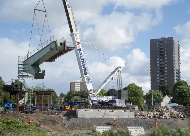 PROJECT:  The giant 60-tonne box-section girder  is hoisted into place.