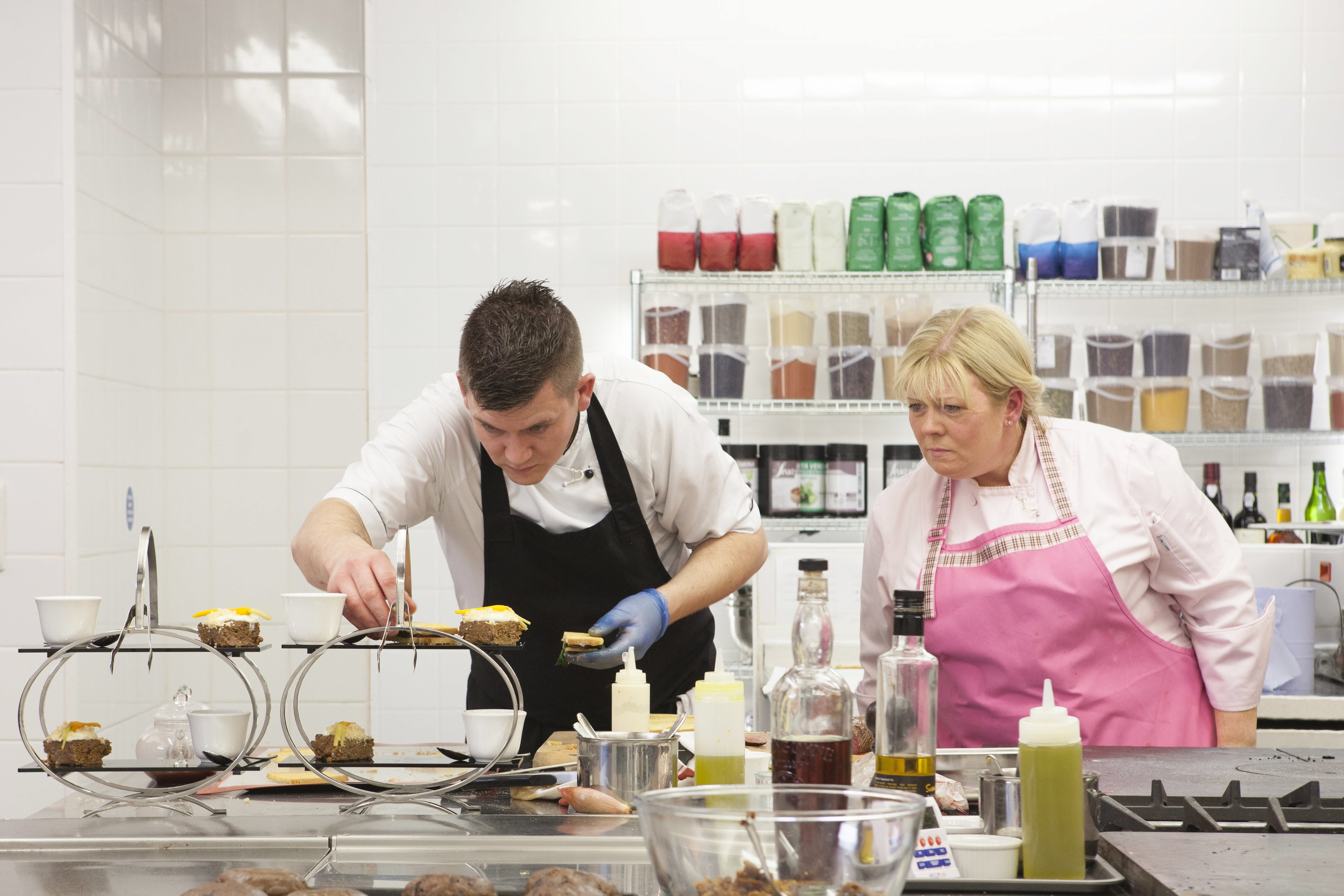 Chef Jak O'Donnell looks on as Graham plates up a dish.