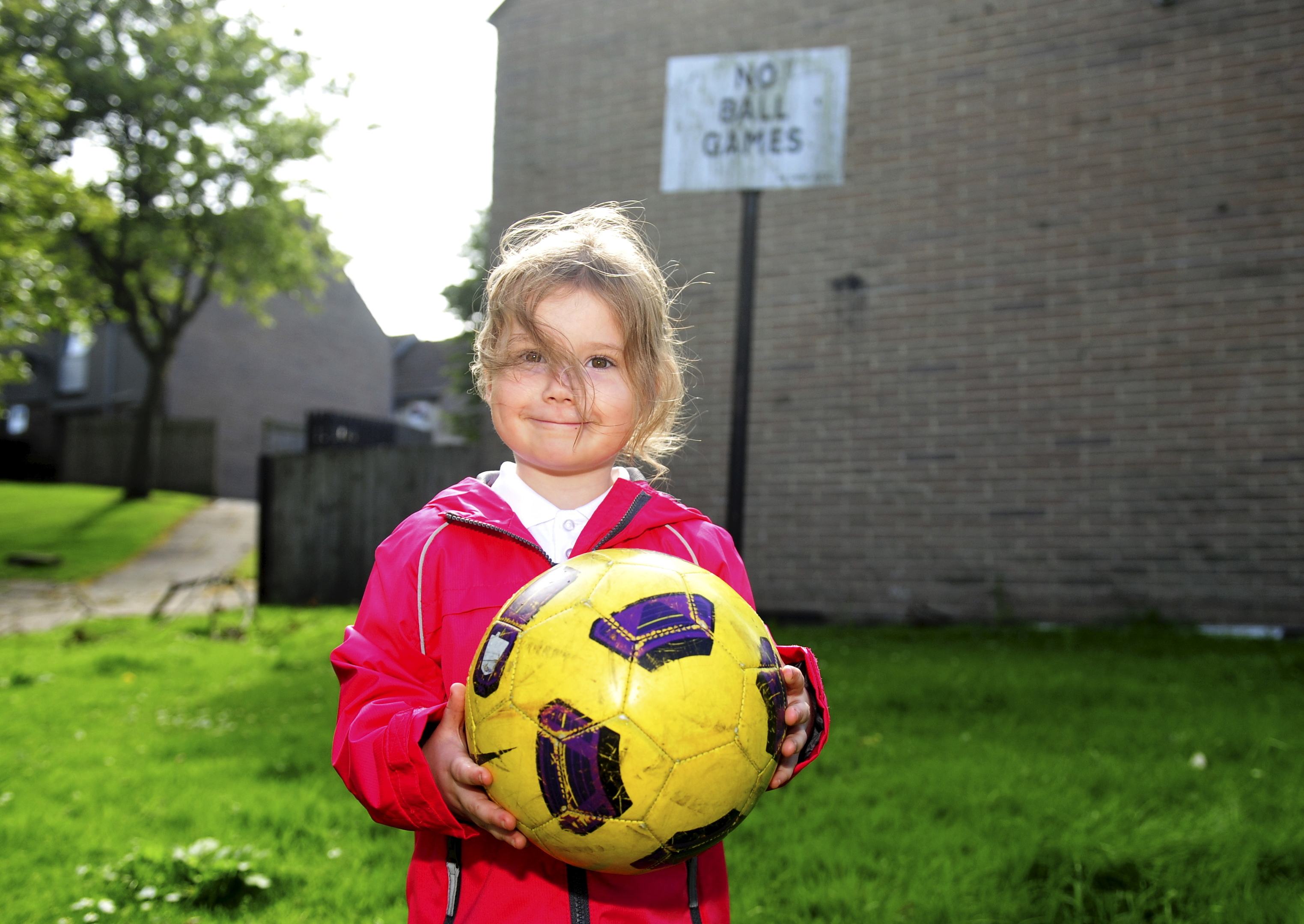 """Kimberly Anderson, 4, plays under a  """"No Ball Games"""" sign on Gordon Mills Crescent in the city's Tillydrone."""