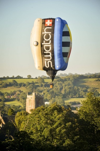 The Swatch shaped hot air balloon hovers near a church tower in a Somerset field during the first mass ascent at the 37th Bristol International Balloon Fiesta . Ben Birchall/PA Wire