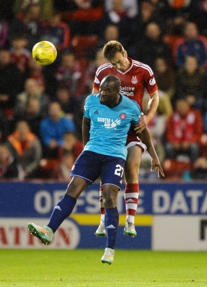 Aberdeen's Andrew Considine goes in for the aerial challenge against Hamilton's Christian Nade (front)