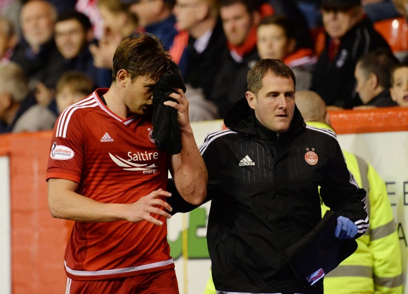 Aberdeen's Ash Taylor receives treatment on the touchline