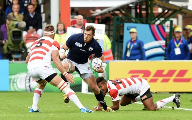 Scotland Sean Lamont tries to skip past the Japan defence.
