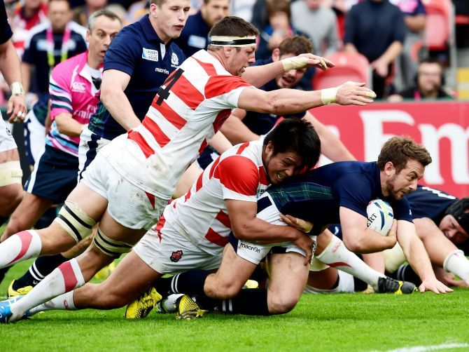 Scotland captain Greig Laidlaw (right) is challenged from Japan's defence.