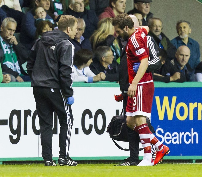 Aberdeen's Graeme Shinnie goes off with an injury early in the first half.