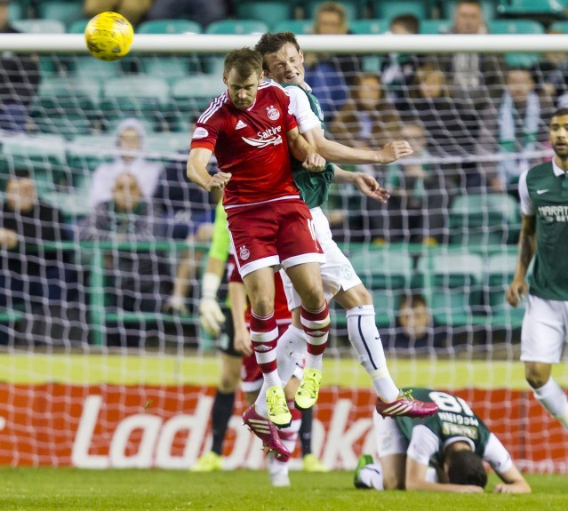 Aberdeen's Niall McGinn (left) battles with Liam Henderson