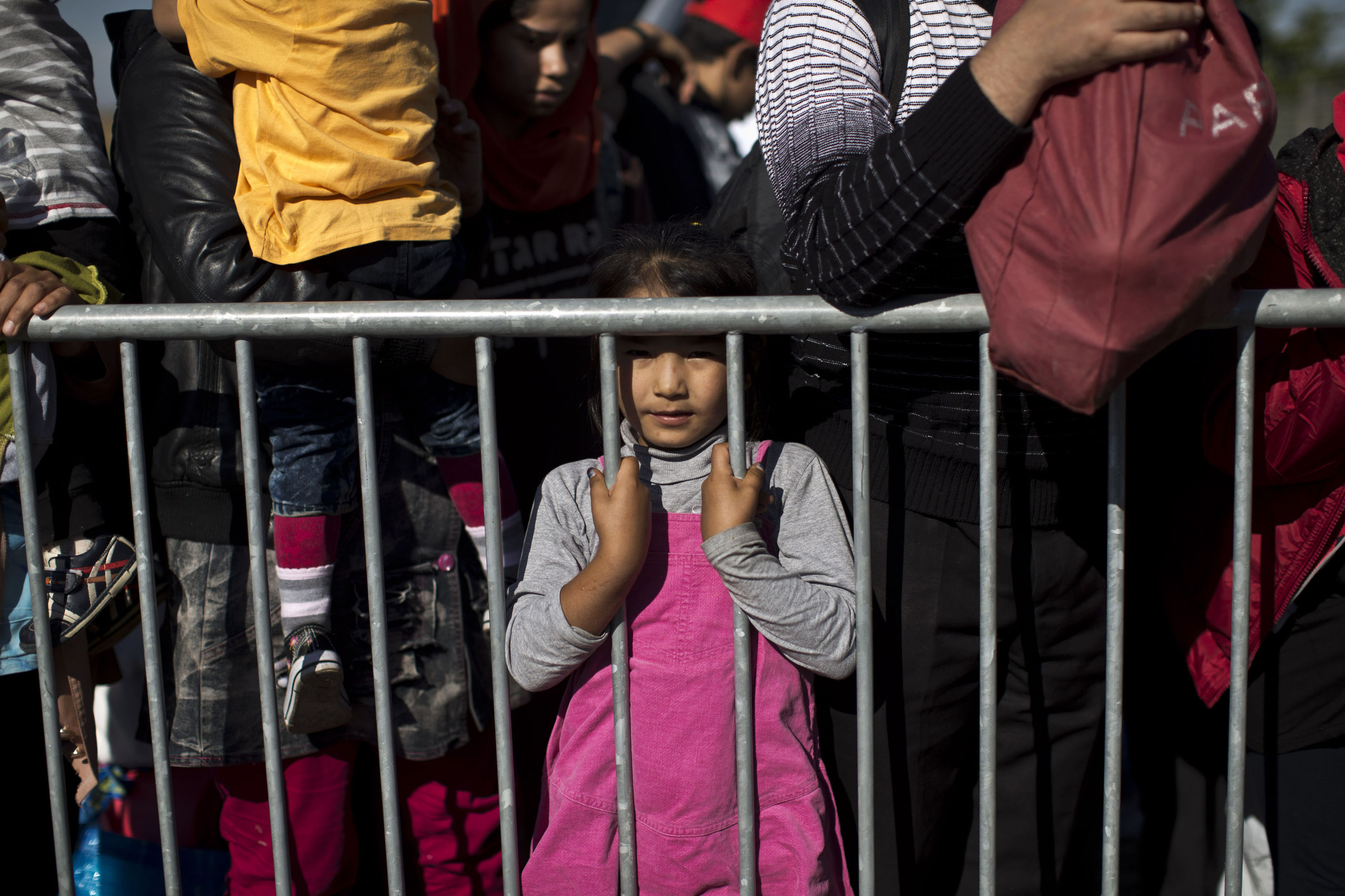 A girl stands behind a barrier as people queue to get into a migrant and refugee reception centre in Croatia.