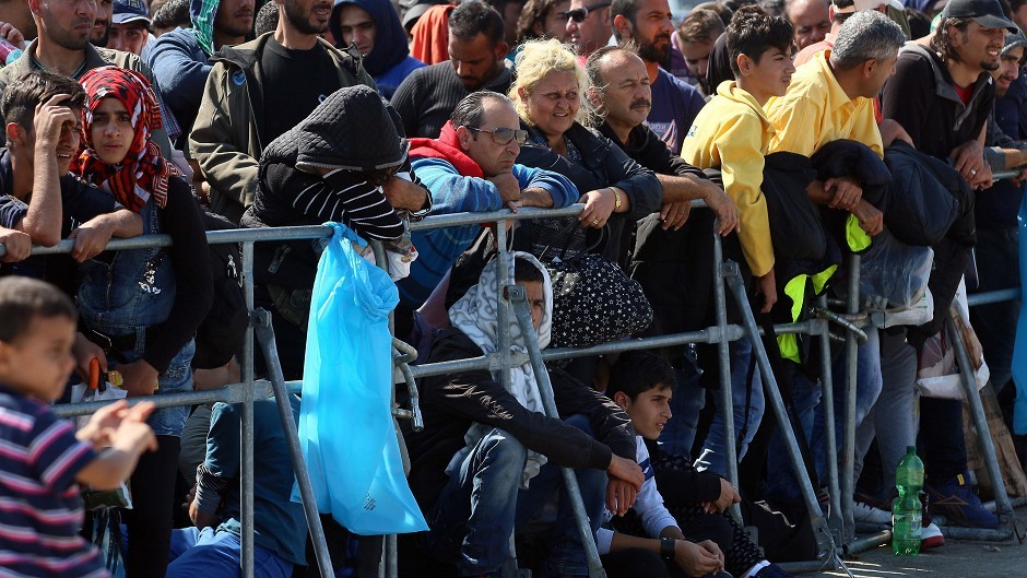 Migrants and refugees wait for buses after crossing the border between Hungary and Austria (AP)