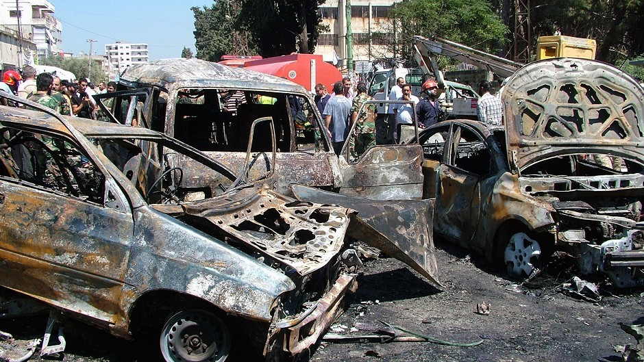 Residents and emergency personnel gather at the site of a car bombing in the port city of Latakia, Syria