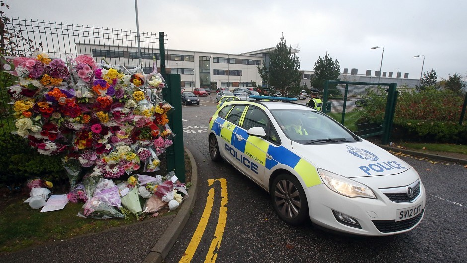 A police car passes floral tributes outside Cults Academy in Aberdeen