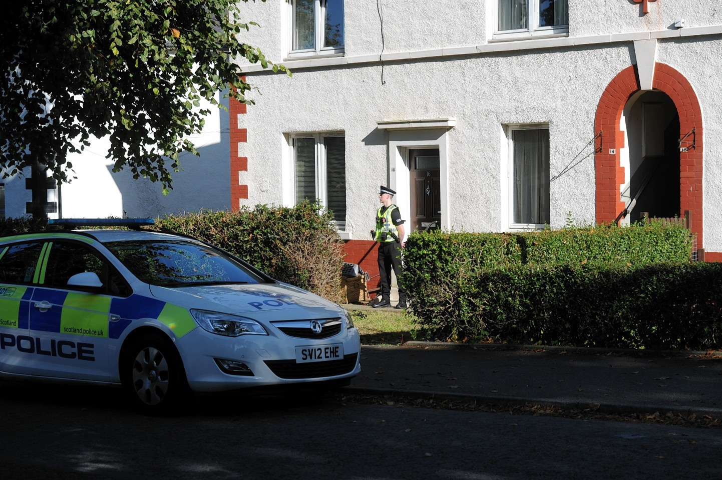 A policeman stands guard outside the flats in Middlefield Terrace, Aberdeen.