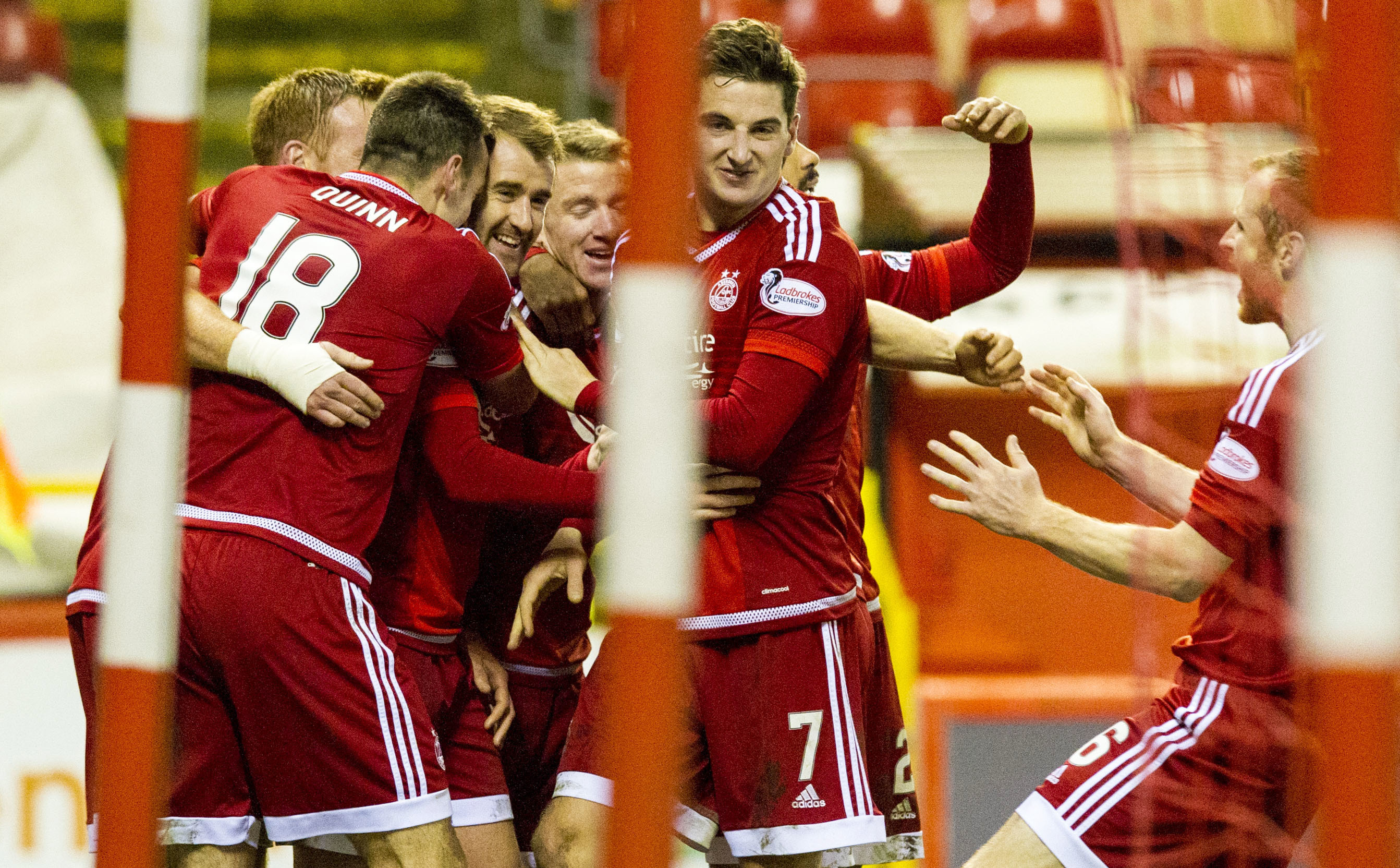 Niall McGinn is mobbed by his team-mates after scoring.