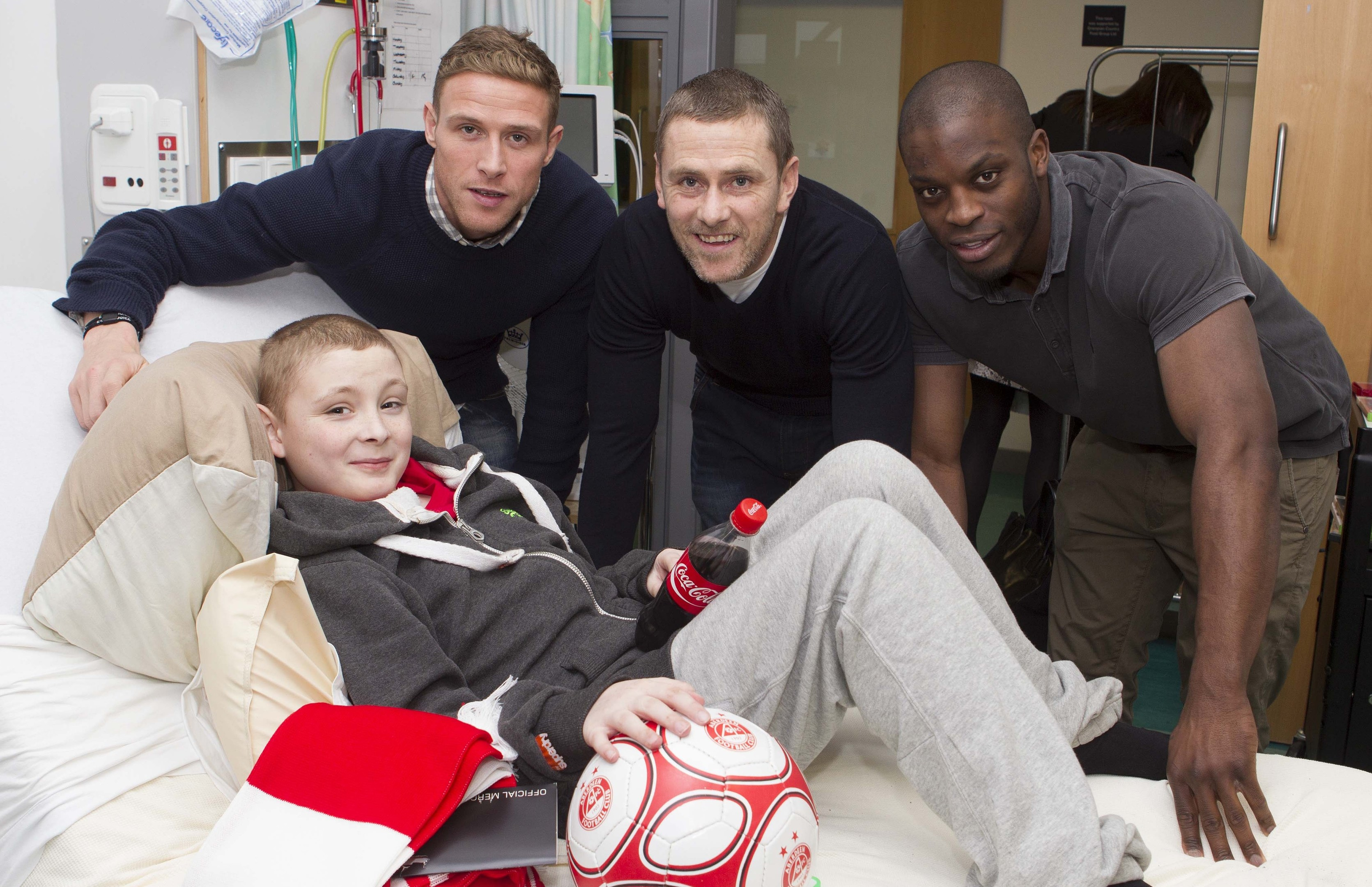 Kain McLeod being visited at Royal Aberdeen Children's Hospital by Dons players Chris Clark, Gary Naysmith and Isaac Osbourne in December 2012.