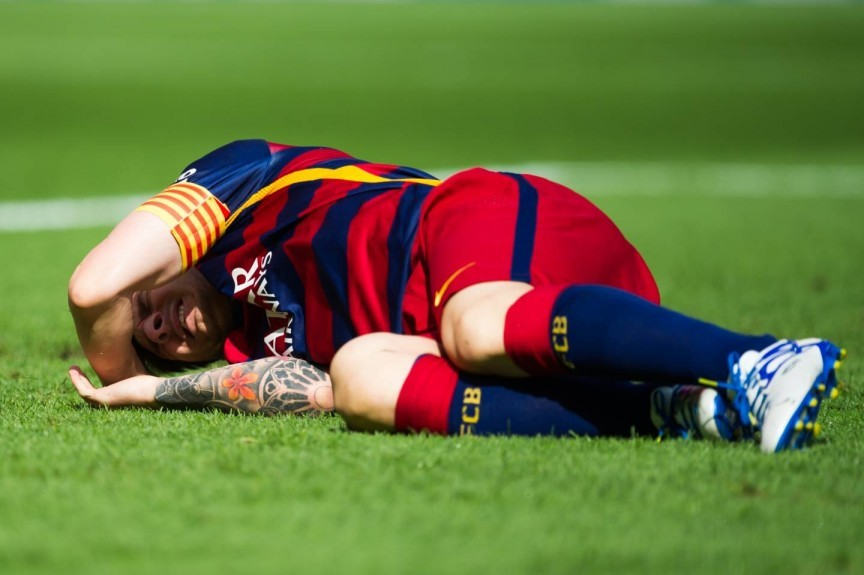 Lionel Messi lays injured on the pitch.