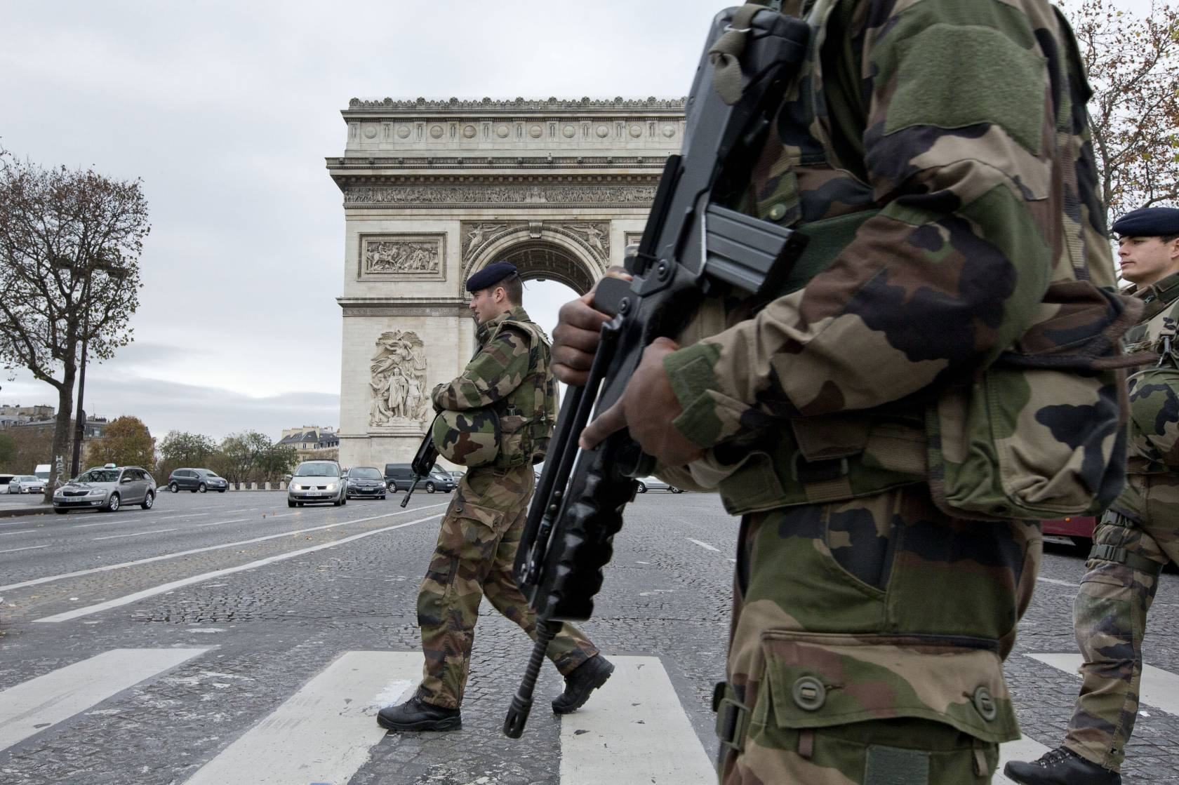 French soldiers cross the Champs Elysees avenue passing the Arc de Triomphe.