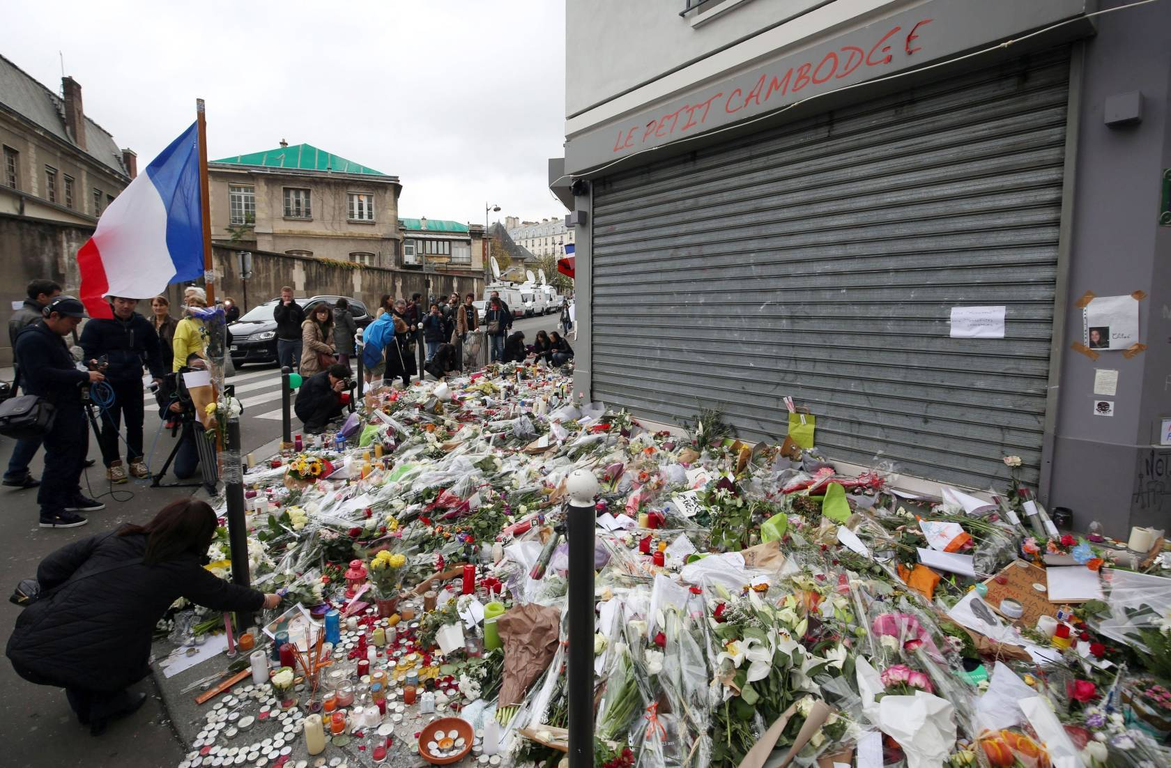 Floral tributes and candles left at Le Petit Cambodge.