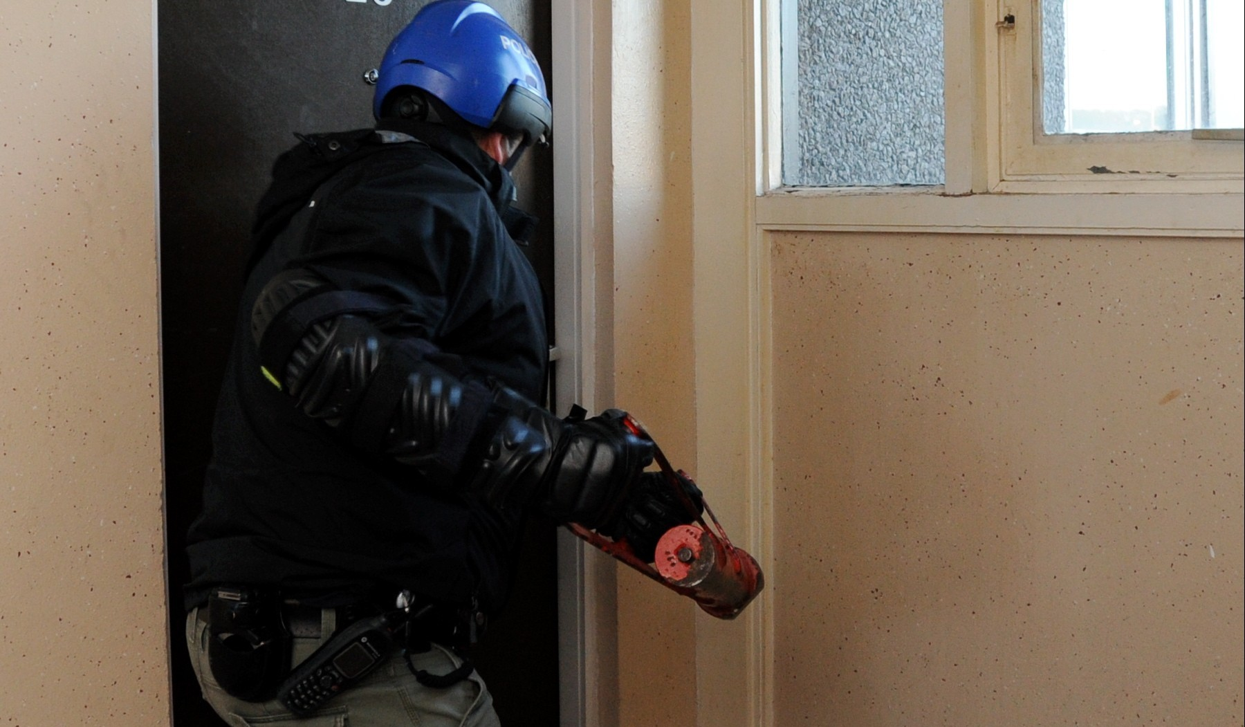 An officer breaks down a door. Pictures by Kath Flannery