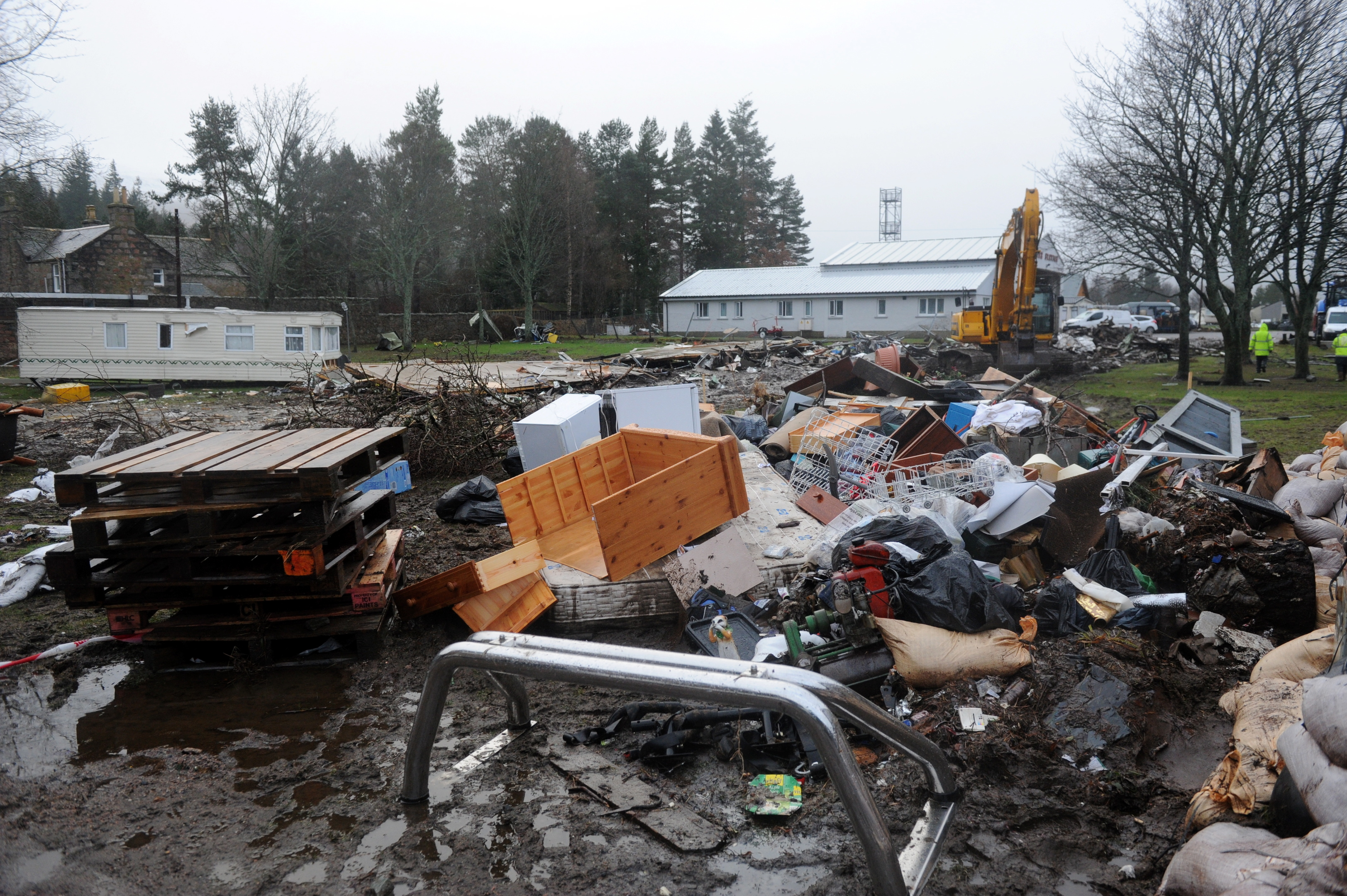 Damage:The aftermath of the flooding at Ballater Caravan Park. Inset left, Mr Savege speaking to business owners and, right, possessions lying on the streets.
