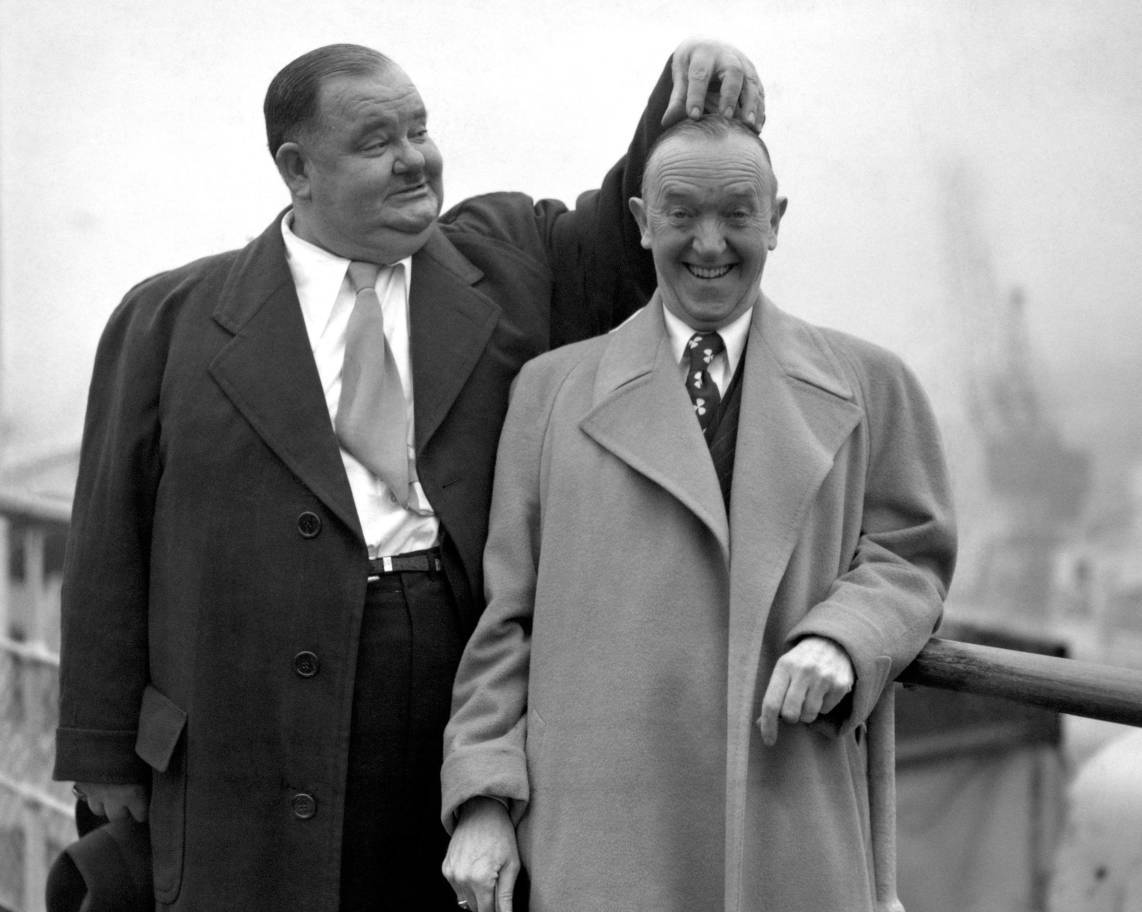 Oliver Hardy scratches the head of comedy partner Stan Laurel