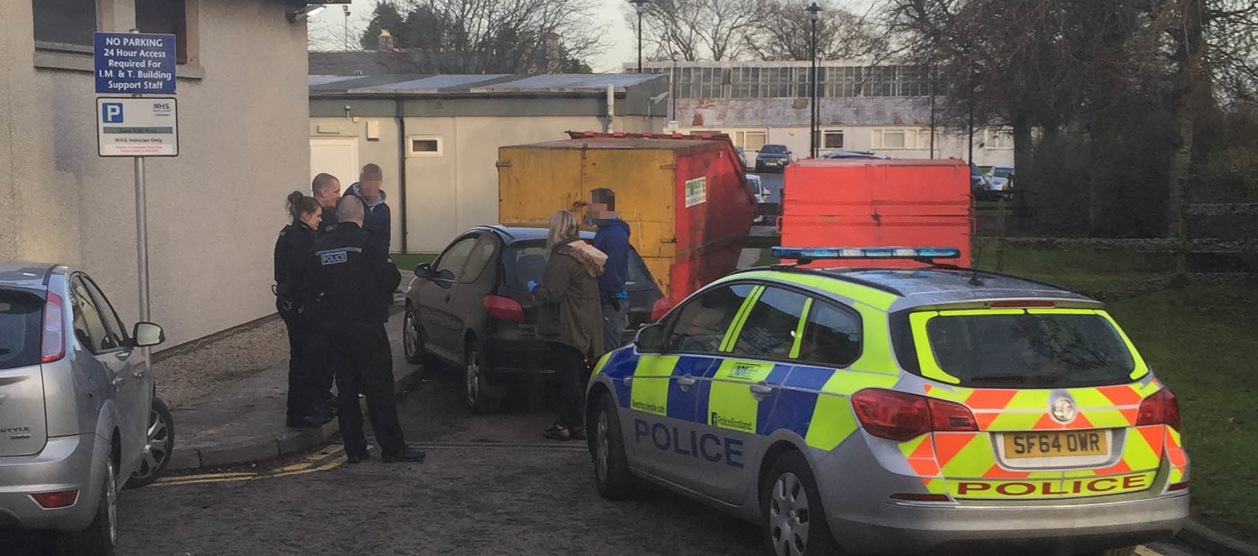 Police officers at the scene after the car crashed into the skip
