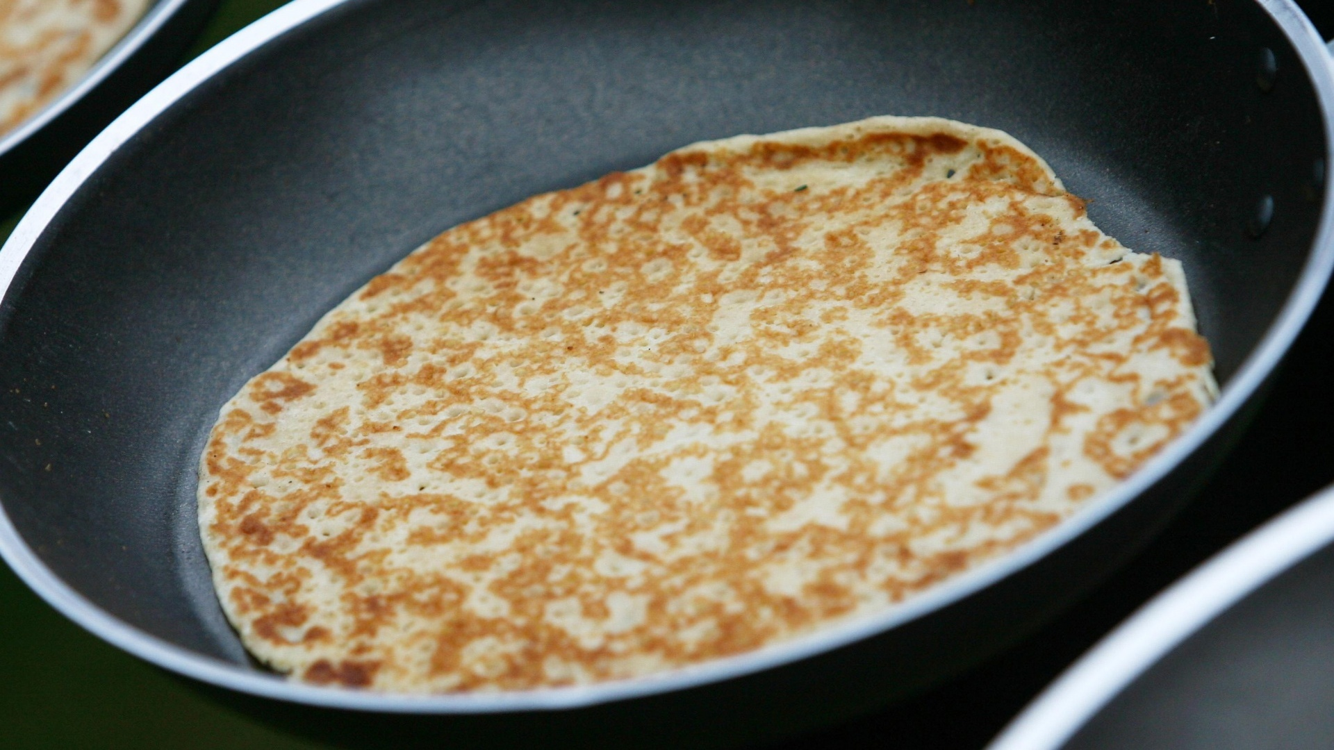 A pancake in a frying pan about to be flipped