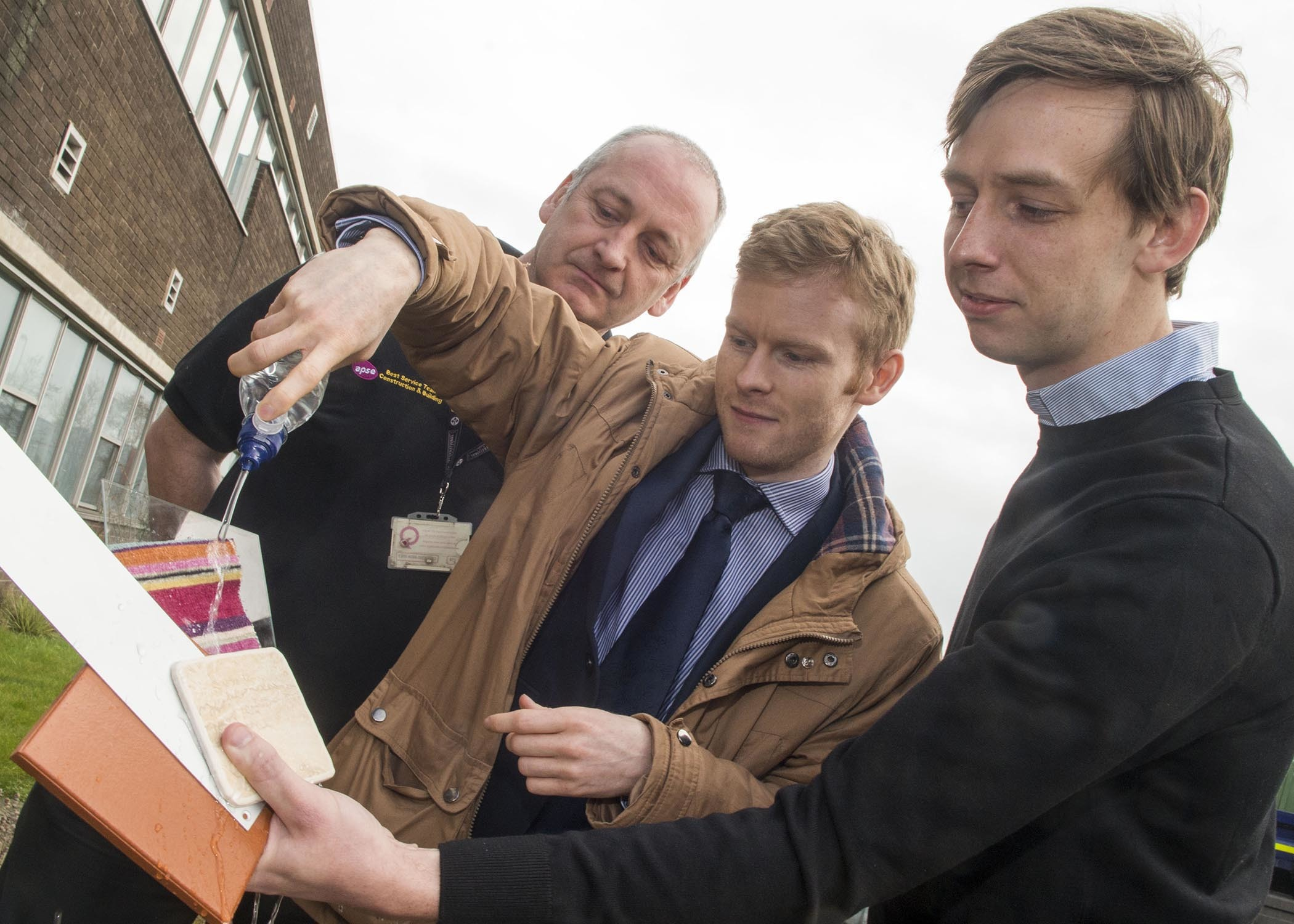 Cllr Ross Grant, centre, tries out the paint with Kenneth Sharp of Ecourea and contracts manager Kenny Don.