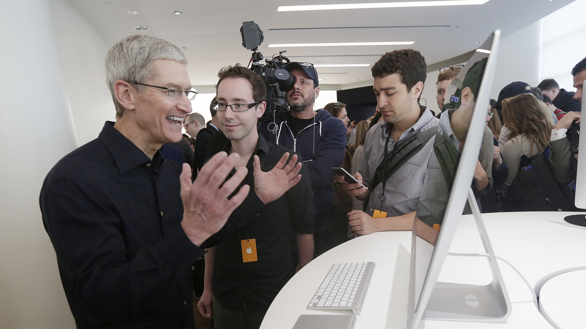 Apple CEO Tim Cook jokes with an employee as he looks at a new iMac