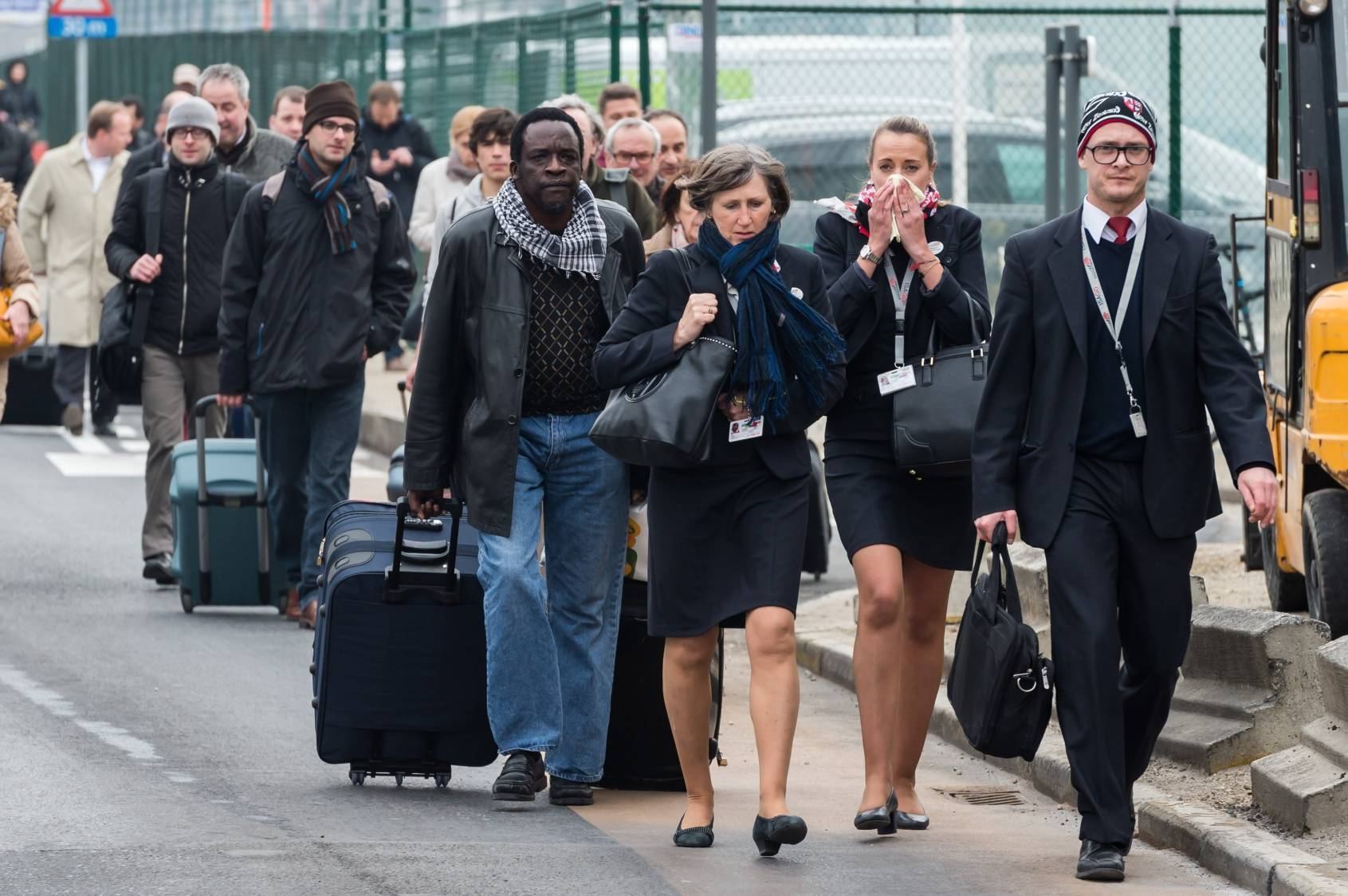 People react as they walk away from Brussels airport after explosions rocked the facility in Brussels.