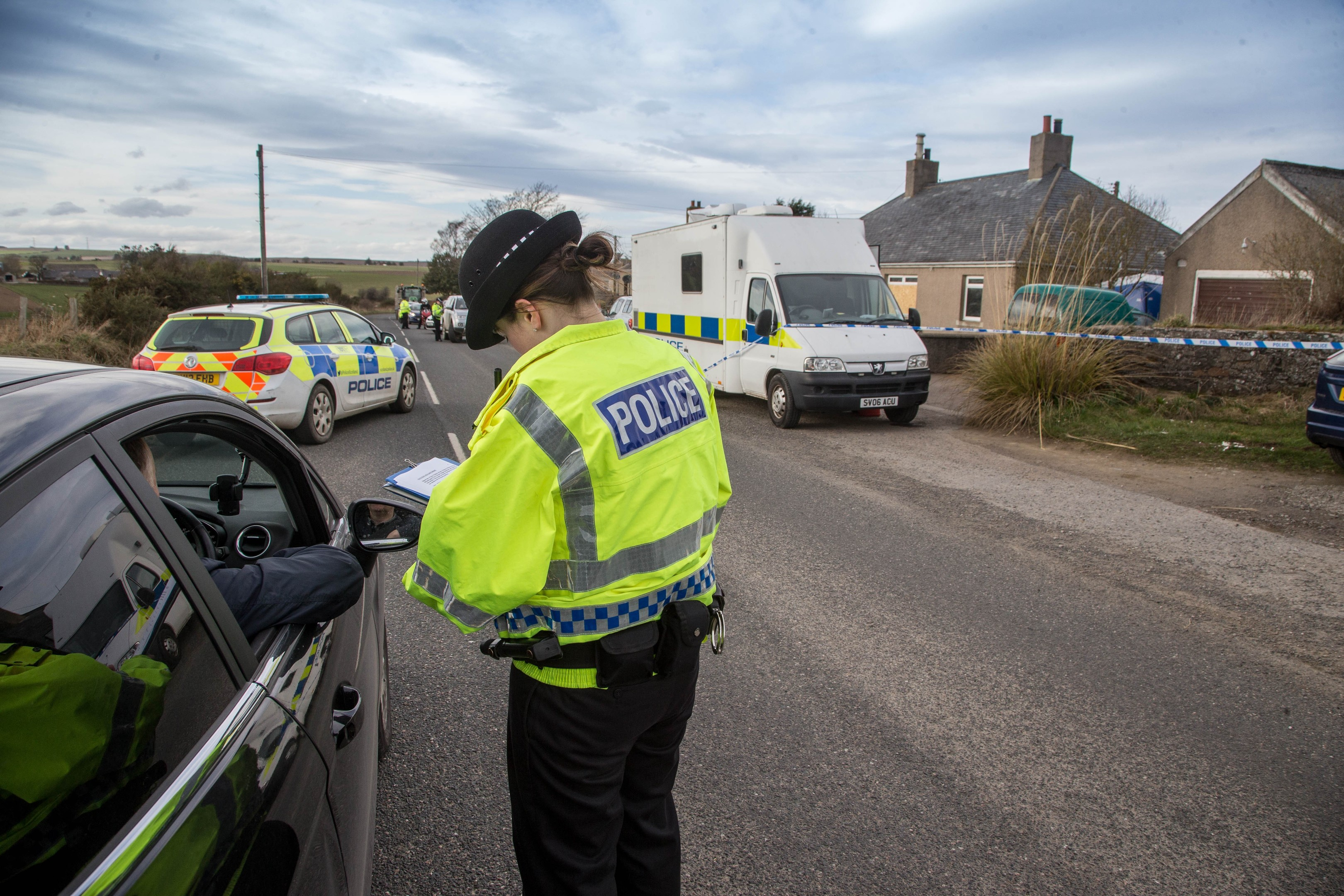 An officer speaks to a driver as police search for clues over the death of Brian McKandie.