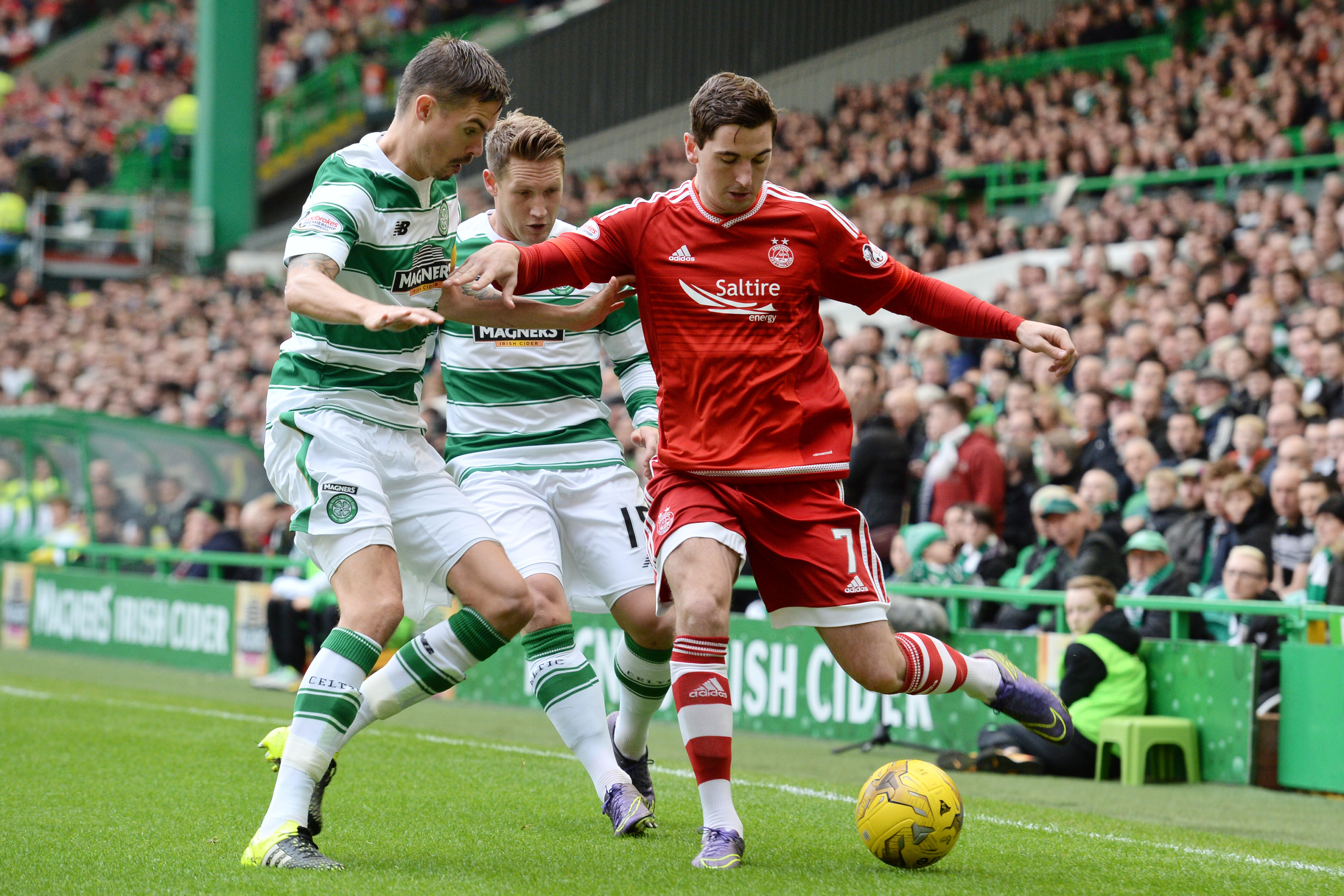 Dons midfielder Kenny McLean under pressure from Celtic's Mikael Lustig, left, and Kris Commons.
