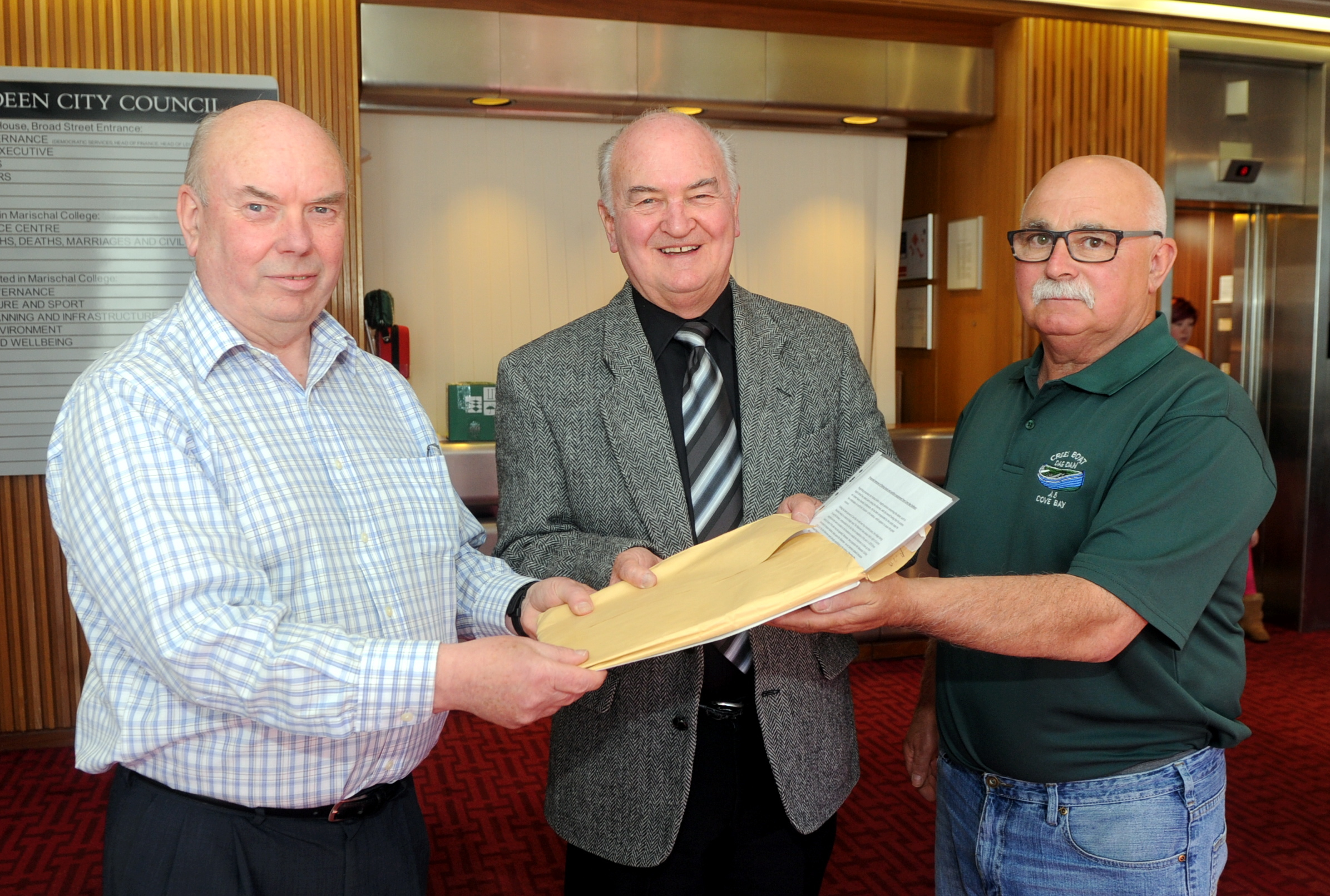 Jim Adam, left, chairman of Cove Fishermen's Association and George Skinner, right,  hand over a petition to Councillor Neil Cooney.