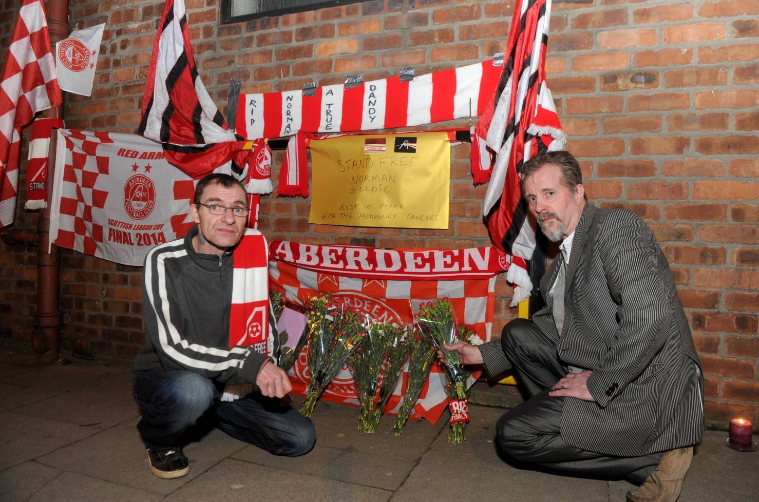 Dons fans Leslie Johns, left, and Fin Hall lay flowers and scarves at Pittodrie in memory of Dons fan Norman Goldie