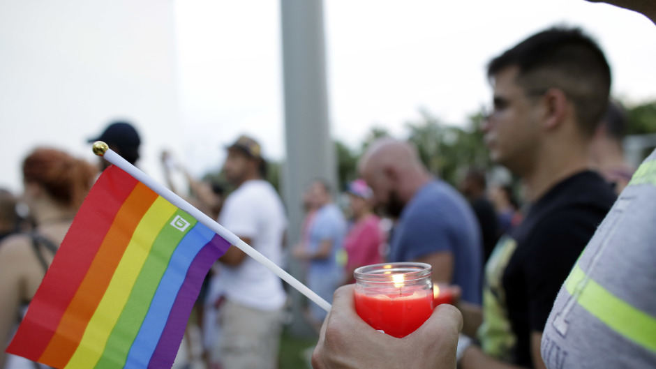 A man holds a candle and a rainbow flag during a vigil in memory of the victims of the Orlando mass shooting, in Miami Beach (AP)