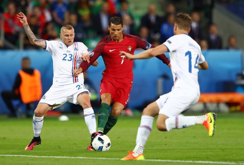 Cristiano Ronaldo of Portugal competes for the ball against Ari Skulason (left) and Kari Arnason of Iceland