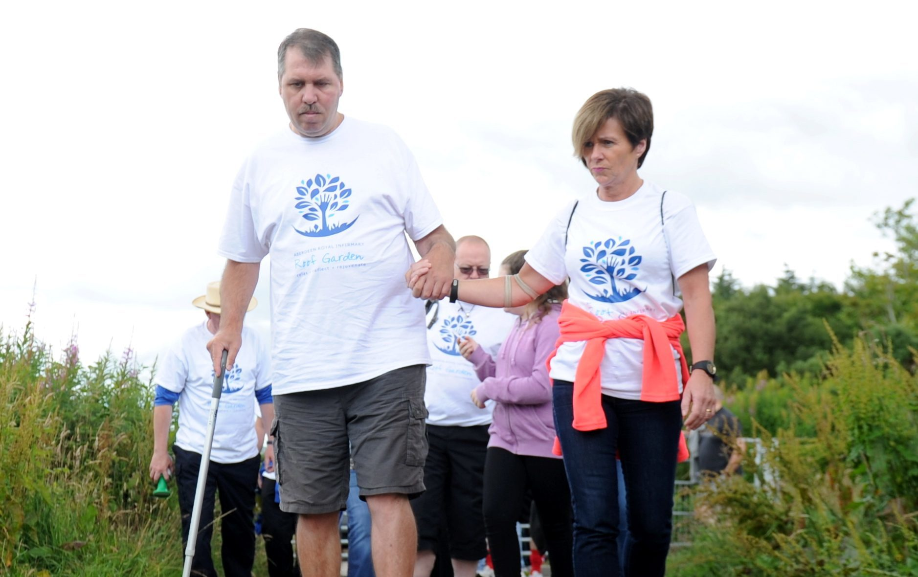 Paul Breen, who has been awarded a BEM, walking up Brimmond Hill with the help of Karen Fyvie to raise money.