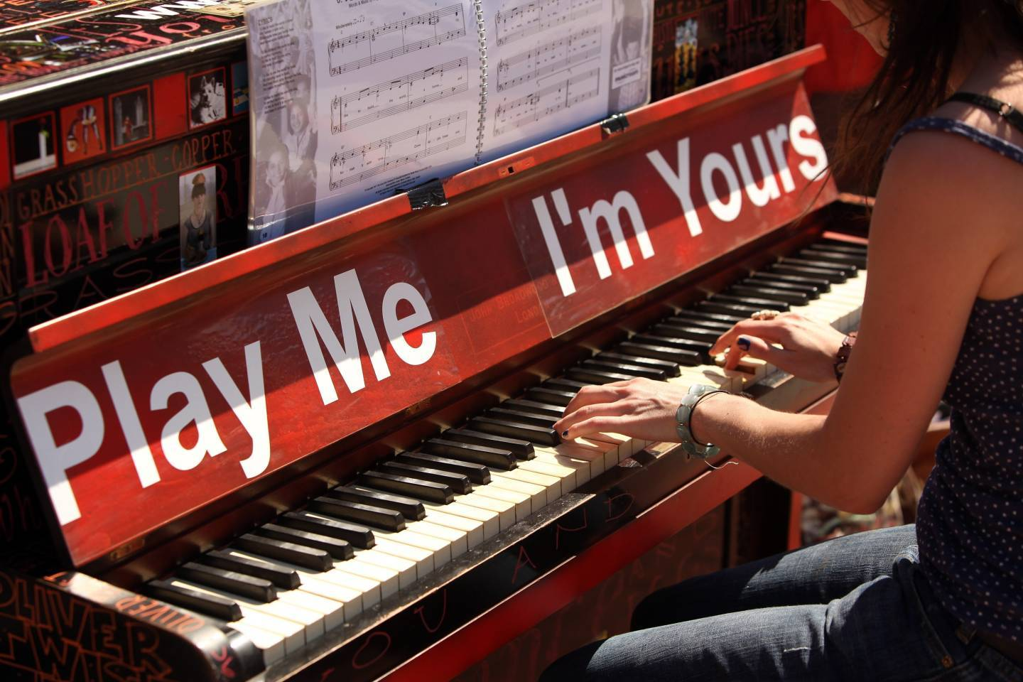 A woman plays the Street Piano placed in front of the British library in London.