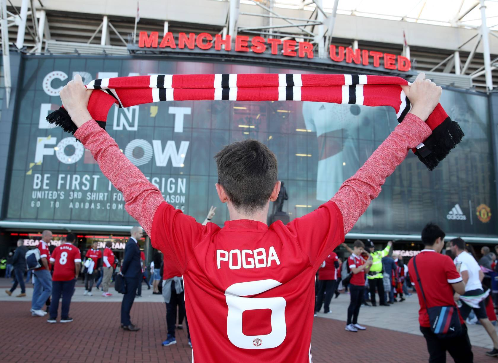 A Manchester United fan celebrates Paul Pogba before the Premier League match at Old Trafford.
