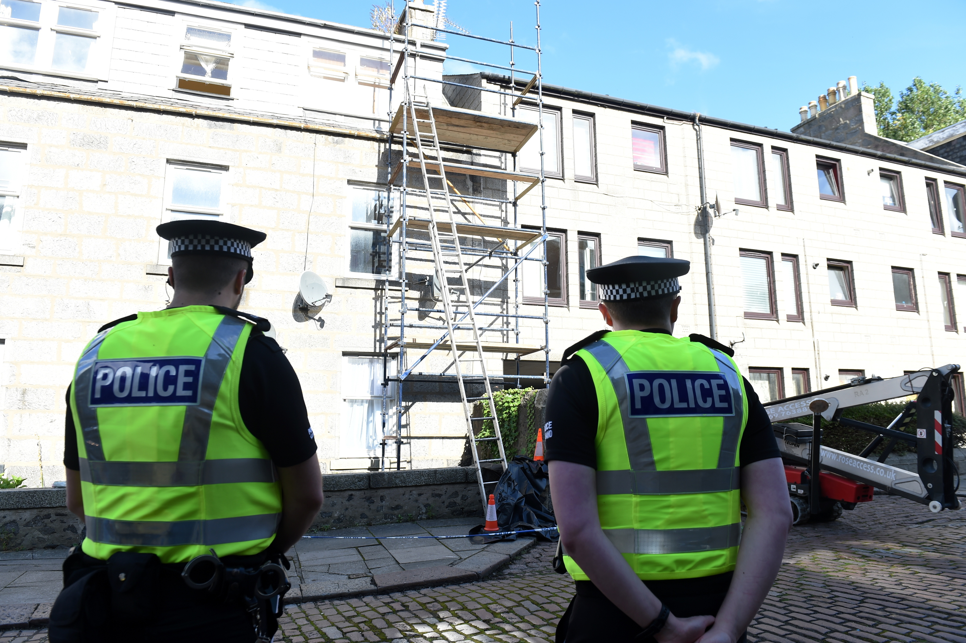 Police officers at the scene after a man died following a fall at Jute Street