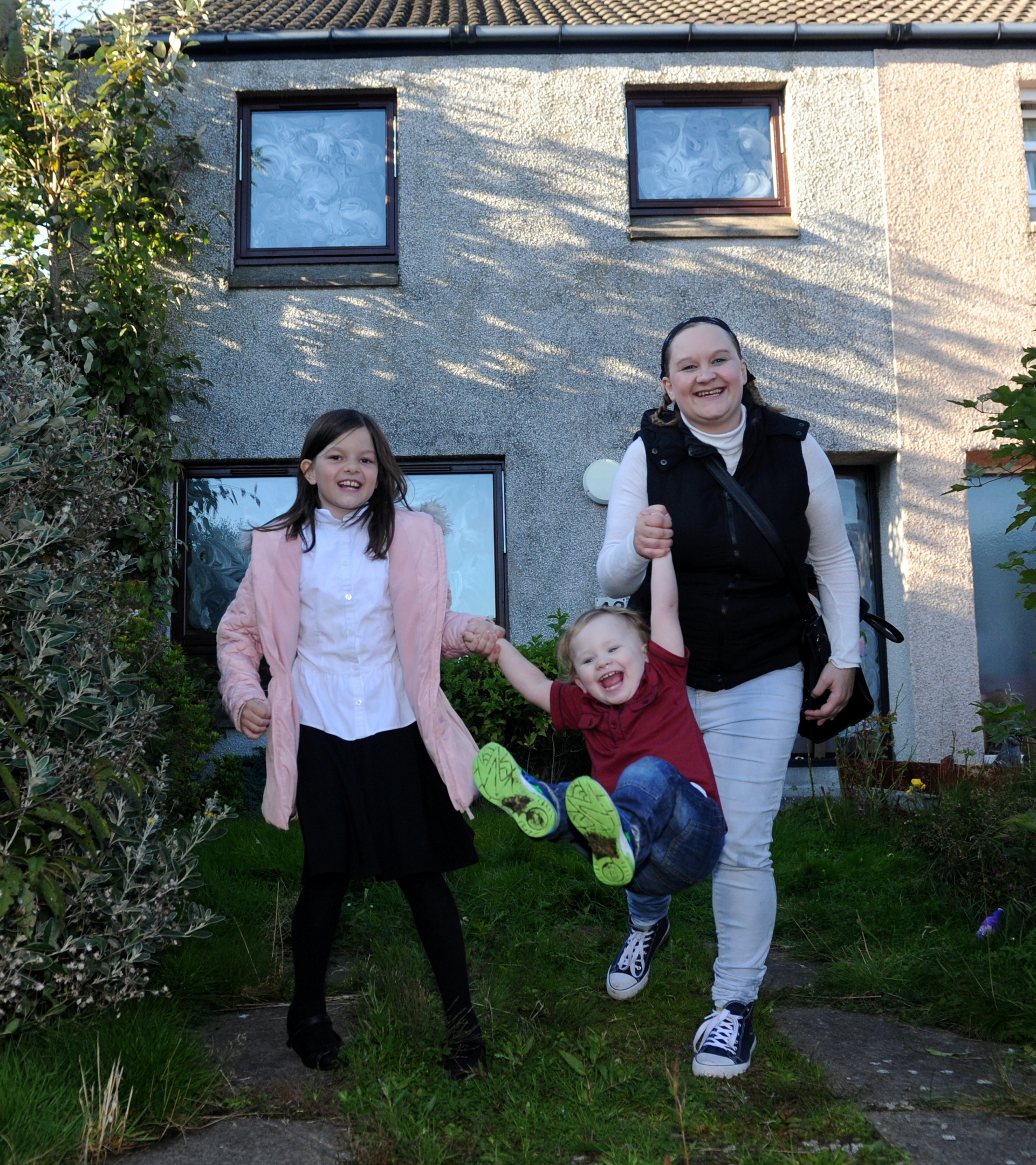 happy:  Donna Crossley with two of her children Shannon Crossley and Cohen Bruce outside their new home.  picture by kath flannery