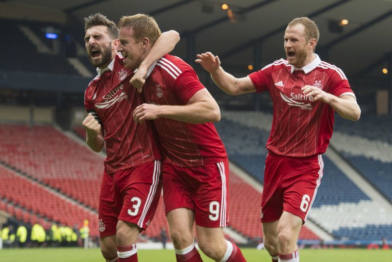 Mark Reynolds (right) celebrates with Graeme Shinnie and Adam Rooney at Hampden.