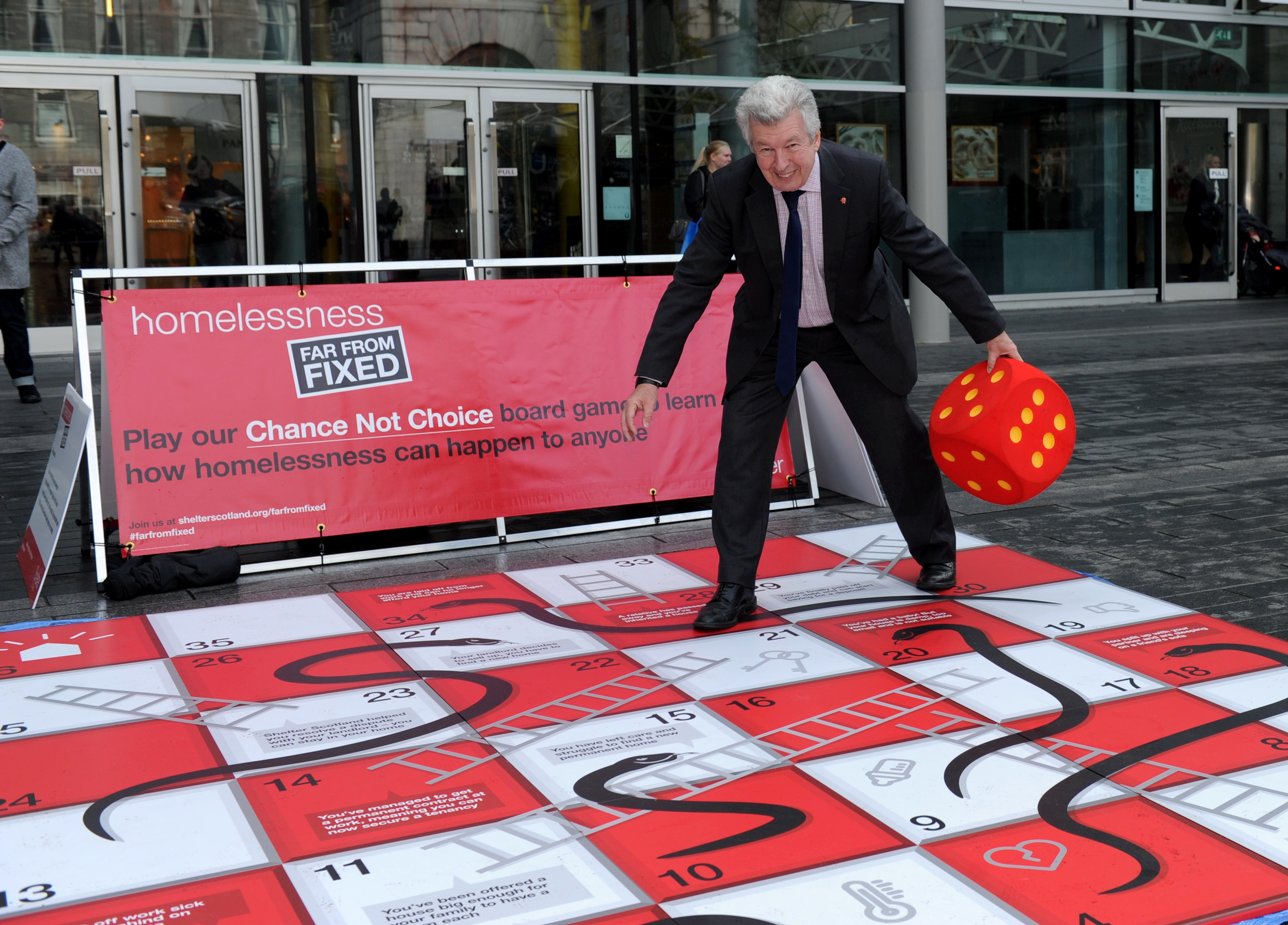 Lewis Macdonald and Jenny Laing play on Shelter's giant snakes and ladders board at Union Square.