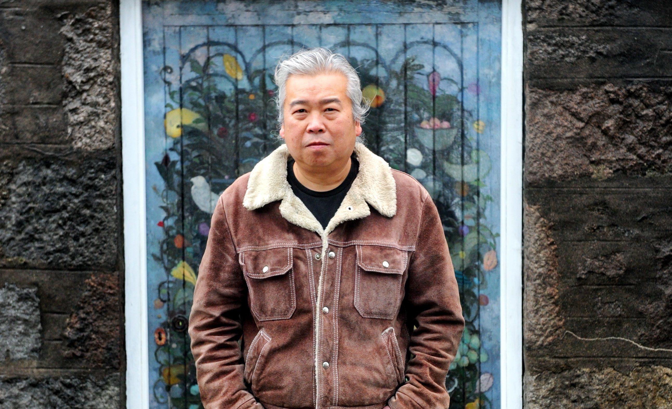 Artist Joe Fan in front of the door he painted  in Langstane Place, Aberdeen.