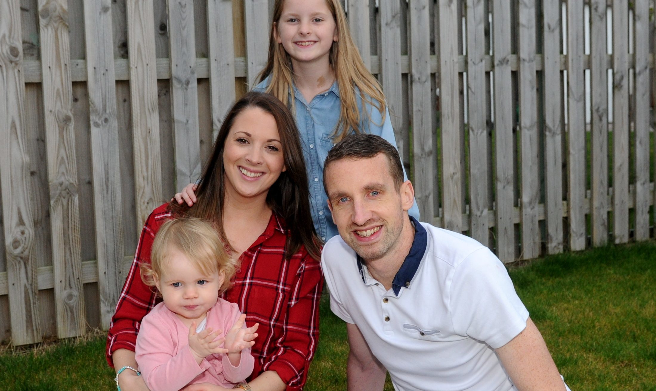 Amy Smith with her children, from left, Elle and Caitlin, and partner Andrew Simpson.